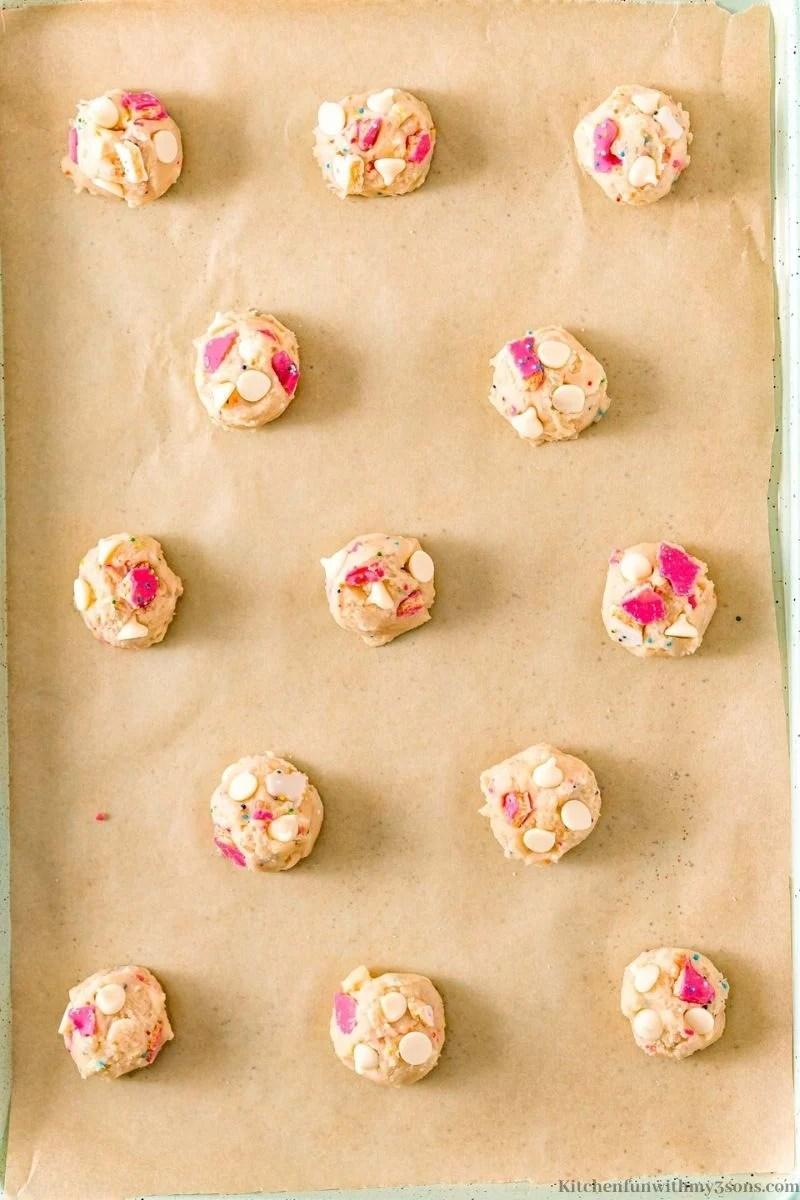 Medium cookie dough balls arranged onto a prepared sheet.