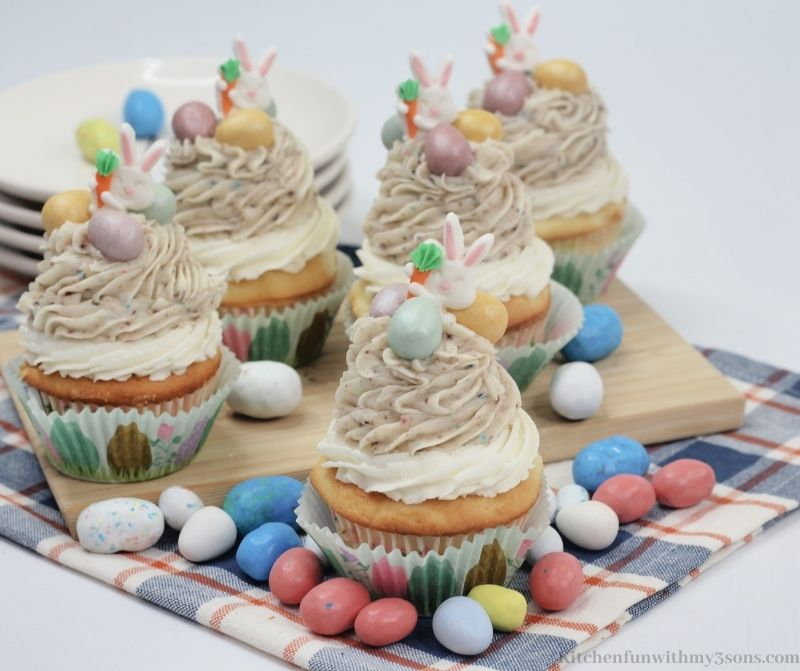 A bunch of the cupcakes on a wooden board.