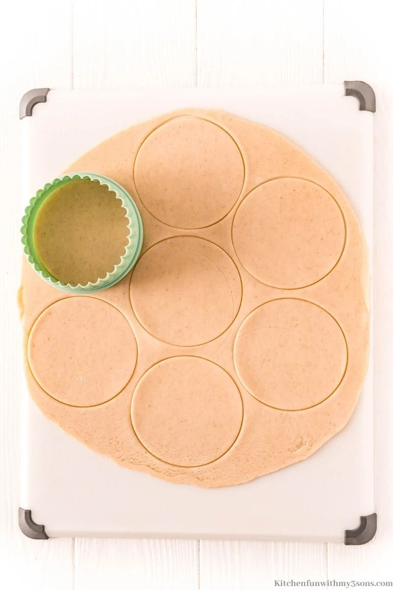 Using a biscuit cutter to cut circles out of the pie crust.