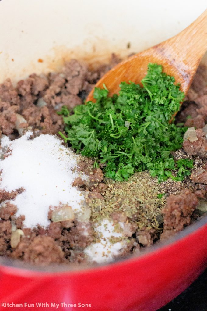 adding fresh parsley and seasonings to cooking meat in the pot.