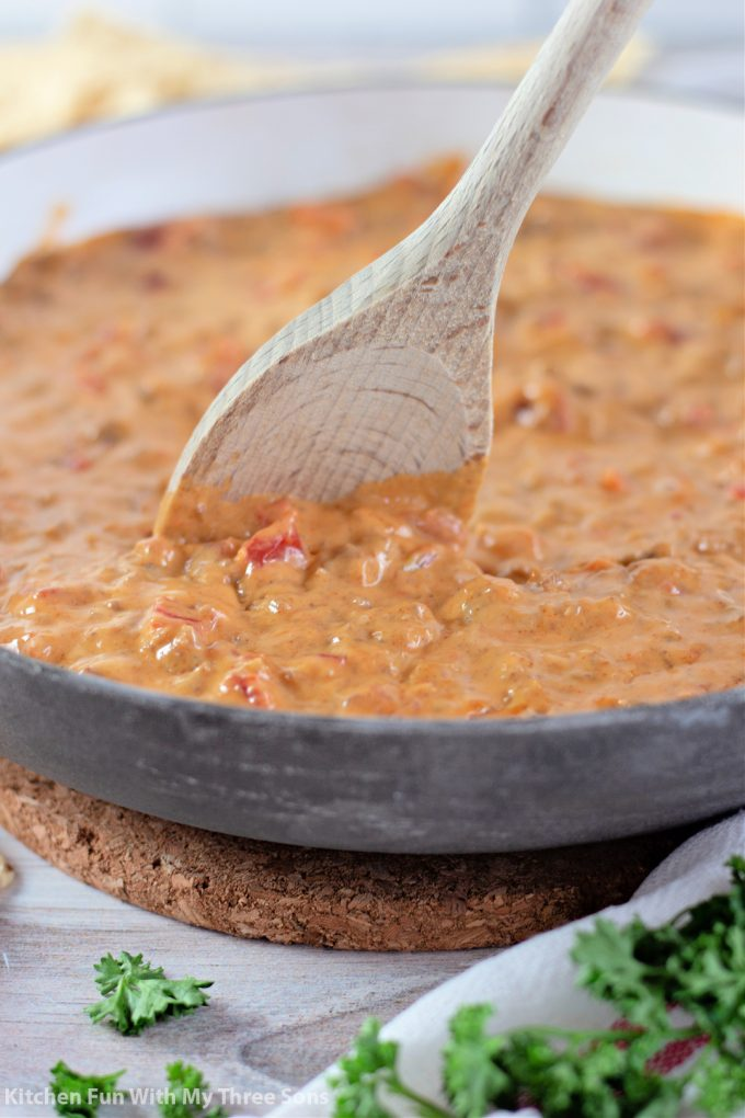 stirring Rotel Dip with Ground Beef in a skillet.
