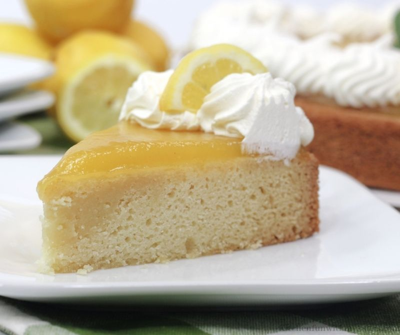 A piece of the cake with some extra lemons on the side.