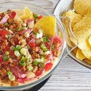 Nacho's en kaasdip met worst, salami, tomaat en bosui
