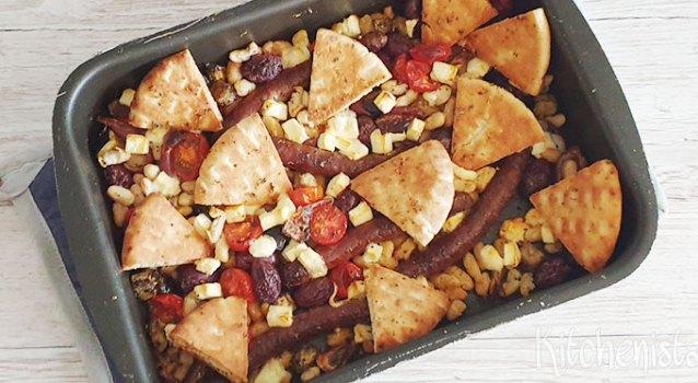 Traybake met worstjes, bonen, aubergine, olijven en pitachips