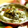 A pretty serving dish of palak paneer is kept on the table