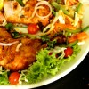 Tandoori chicken is placed in a platter with a lot of greens and other vegetables