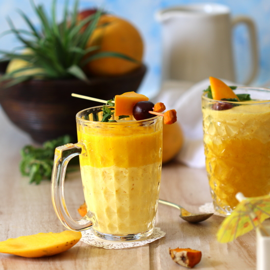 the mango smoothie is served in pretty glass bowls