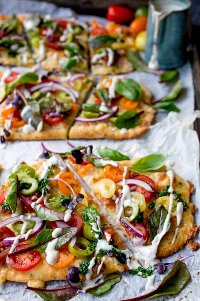 This Vegetarian Summer Tomato Pizza with Basil Garlic Butter and creamy cashew drizzle is a meal even the meat-eaters will love. The homemade no-knead, no-prove flatbread base is super quick to make!