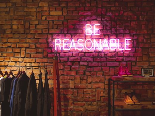 "Exposed brick wall with a neon sigh that says ""Be Reasonable"" in all caps. In front of the wall are racks with shoes and clothes"