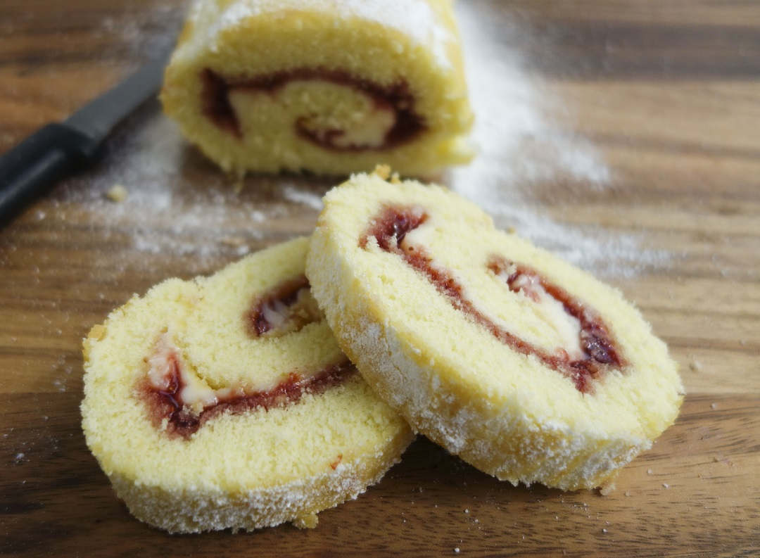 A delicious roulade made with a light summer sponge cake filled with strawberry jam and cream cheese frosting and generously dusted with powdered sugar. Makes a perfect treat for summer parties.