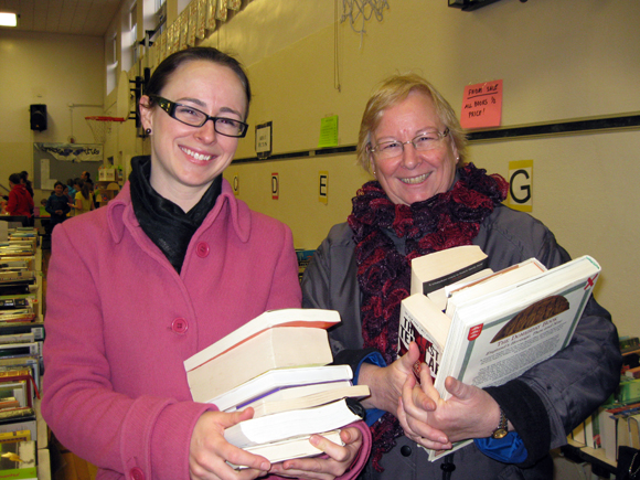 """Barbara Lance (right), of Mayfair Avenue, invited daughter Elizabeth Lance, now of Gatineau, to BookFest. """"I wouldn't miss this for anything,"""" says Elizabeth. Barbara says: """"I bought murder mysteries for summer reading, and non-fiction coffee table books to support my family history habit."""" Elizabeth tracked down novels, books about dogs and business books, including Seth Godin's <em>Purple Cow</em>, but says she's most looking forward to rereading John Grogan's <em>Marley and Me.</em> """"I already have this in digital format, but there's no substitute for a real book."""" Photo by Denise Deby."""