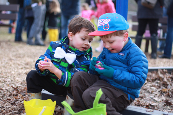 Four year-old friends Evan O'Brien (left) and Jacob Hatcher compare their treasure after hunting for eggs in McKellar Park. Photo by Anita Grace.