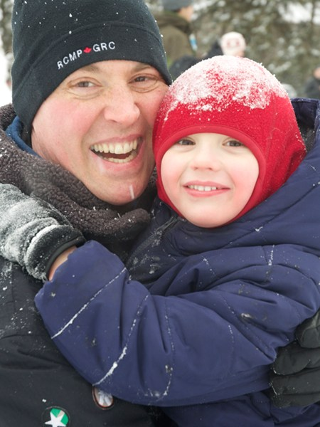 Despite the cold, CJ Angel and his four-year old son, Jack, had a great time at the winter carnival at Woodroffe Park. Photo by Andrea Tomkins