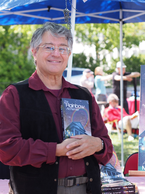 """I've sold three books, I'm happy.… there's 150 authors here – some really far out authors – so if I sell 3-5 books today I'm happy,"" said Martin Bueno, Kitchissippi resident and author of Rainbow Alchemist. Photo by Pearl Pirie."
