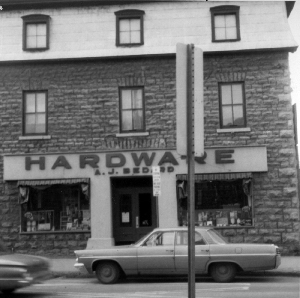 """The """"Magee House"""" has a long history in Hintonburg. Here it is in 1965, when it was the location of A.J. Bedard Hardware. Photo courtesy of the City of Ottawa Archives (CA-24326)"""