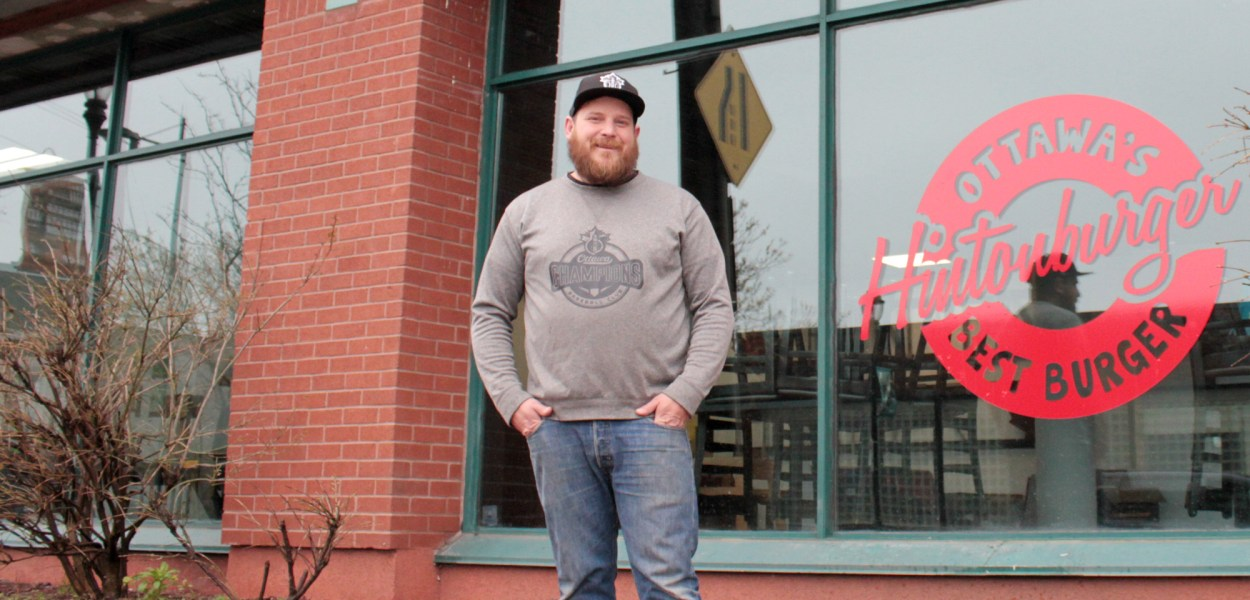 Hintonburger owner Thomas Williams stands in front of his new location at the corner of Bayswater and Somerset St.