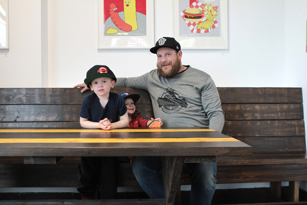 Hintonburger owner Thomas Williams sits with his sons Cecil, 4, and Cameron, 2, at one of the restaurant's new tables made by Kemptville carpenter Larry Gorton. Photo by Jacob Hoytema