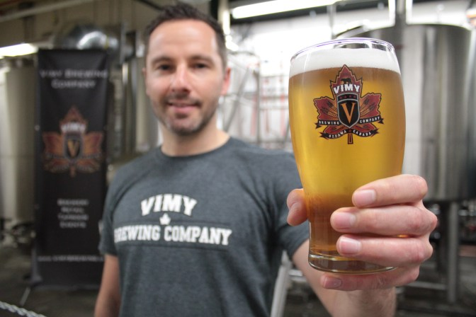Vimy Brewing Company co-owner and -founder Kevin Sirko holds up a glass of the Vimy Cream Ale in their new facility at 145 Loretta Ave. N.