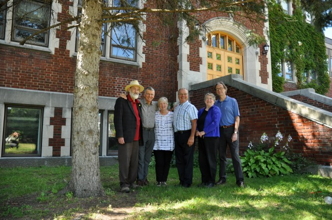 (L-R) Peter MacKinnon, Ian Ramsay, Margaret Haines, Bill Cowie, Martha Aksim, Bruce MacLeod pictured next to one of the evergreens their graduating class planted at Nepean High School. Photo by Andrea Tomkins