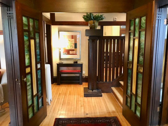 The foyer, seen just as a visitor enters the home. The stained glass doors are original