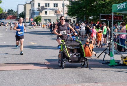 Sarah-Dawn Norris pushes through the finish line with two kiddos along for the ride