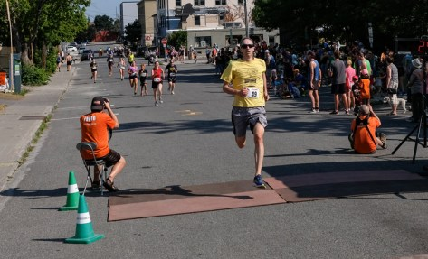 David Cocking crosses the finish with a long trail of runners in tow