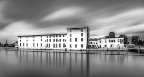 """""""Reflection of building on water"""" by Mitch Gosselin"""