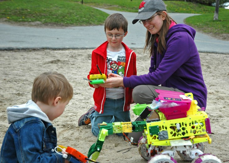 Erin Kennedy shows Miles and Theo Columbus how her beach cleaning bots work.