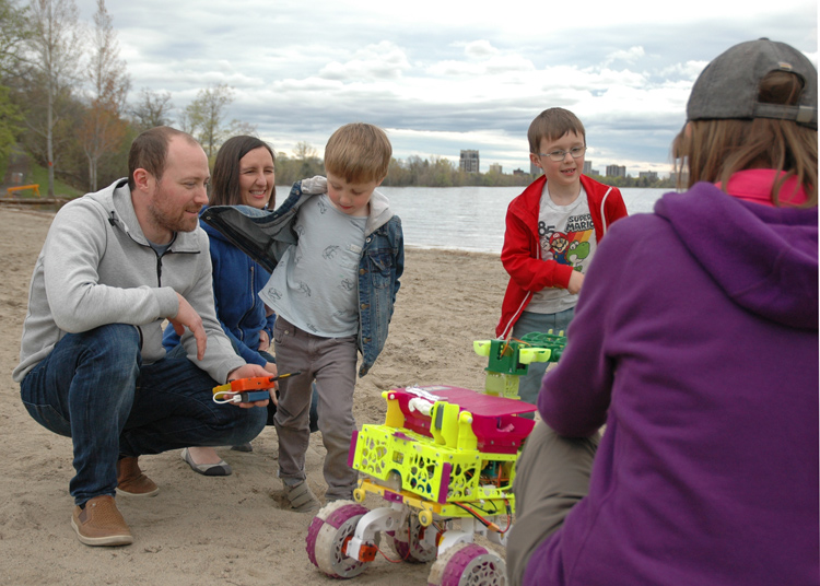 Owen Columbus, Magdalena Columbus and their sons Theo and Miles gather around the bots as Erin explains how they work.
