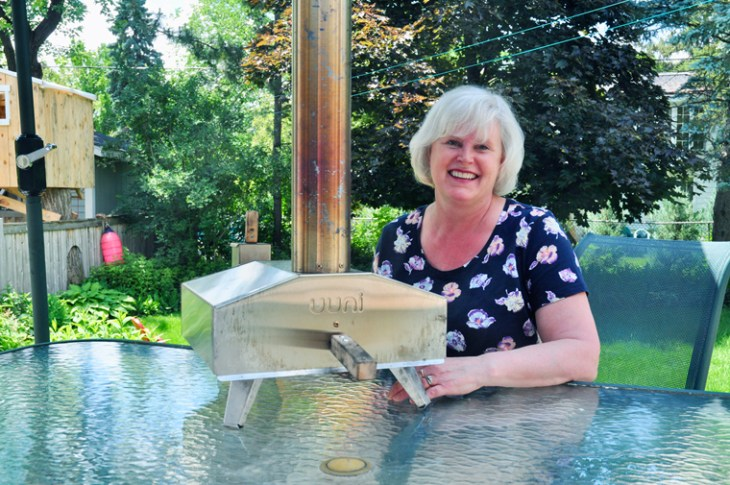 Like many people, food writer Paula Roy's love affair with pizza dates back to her childhood. Her taste buds have matured since then! She's pictured here with her portable backyard pizza oven. Photo by Andrea Tomkins
