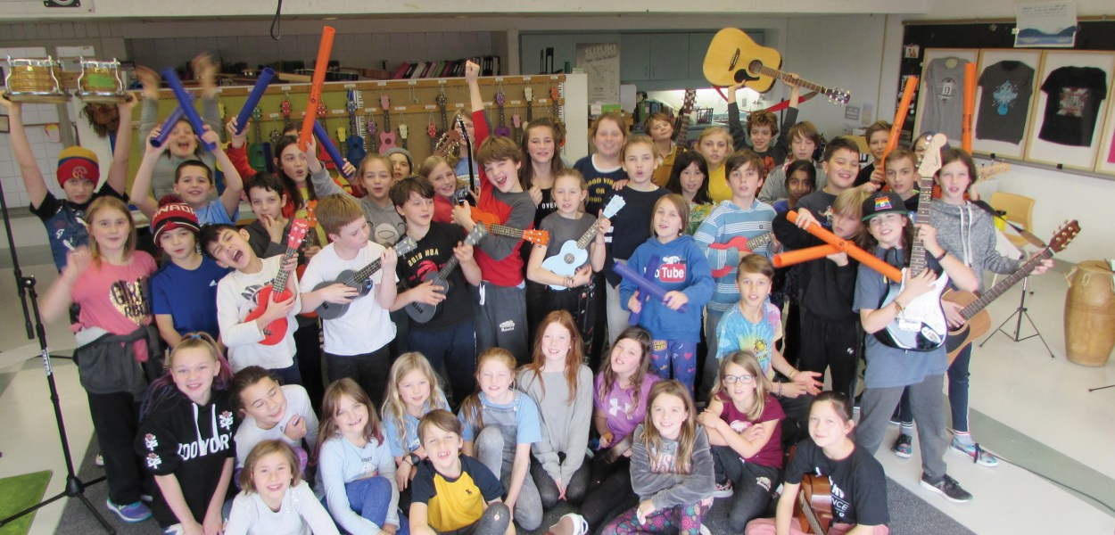 Students from the School of Rock program, with their instruments, at Churchill Alternative School.