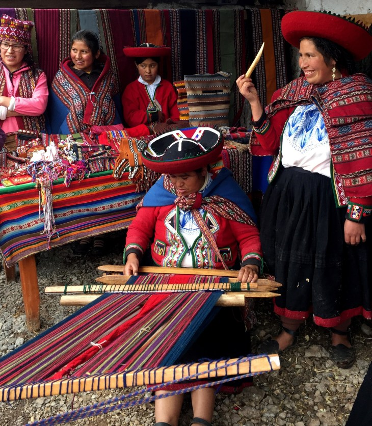 Peruvian women demonstrate weaving techniques.