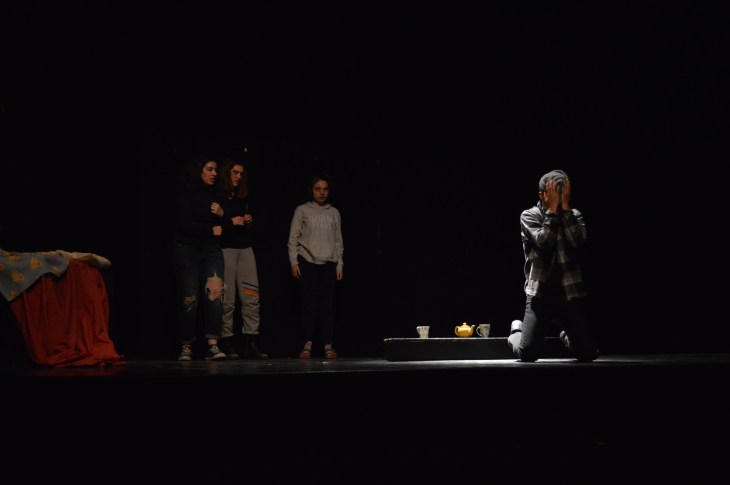 Braeden Moore (center) crouches in despair as Jada Badawy (left), Anna Carsley-Jones (middle) and Katie Laperle (right) watch on during the performance of the student-led play State of Mind.