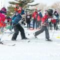 Dressed warmly, three kids set off on a cross-country ski race.