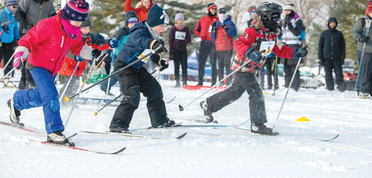 Dressed warmly, three kids set off on a cross-country ski race.
