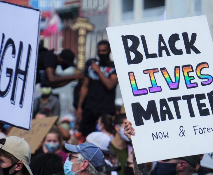 "A white posterboard with the text ""Black Lives Matter"" written in black and rainbow lettering"