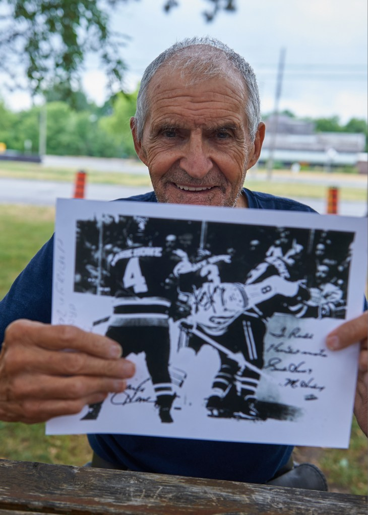 A photo of Rod Zaine holding up a picture of himself playing hockey against Gordie Howe and his sons Mark and Marty.
