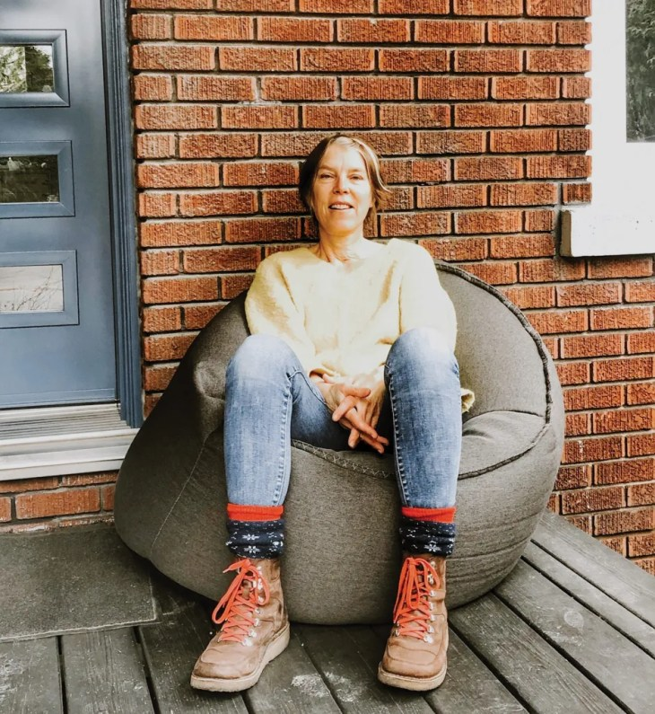 Tina Le Moine sitting in a bean bag chair in front of her brick house.