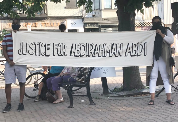 Two organizers holding a banner at 55 Hilda St. on the fourth anniversary of Abdi's death in July 2020.