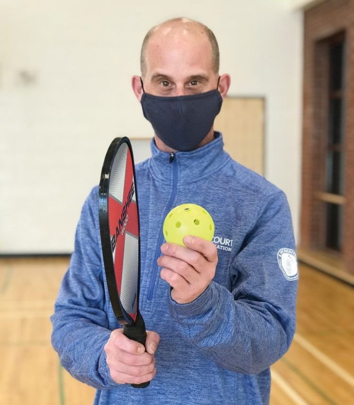 A male instructor in a mask holds a pickleball racket and ball at Dovercourt Recreation Centre