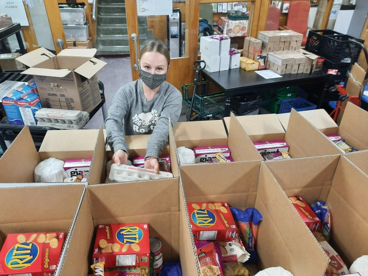 A volunteer fills boxes with food at Ottawa West Community Support's office.