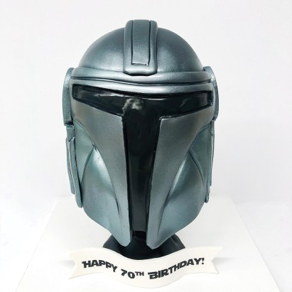 A 3D cake of a silver Star Wars mask.