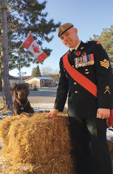 A photo of Randy Turner in uniform outside with his dog.