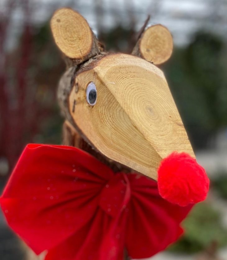 A wooden deer with a red nose stands at Parkdale Market.