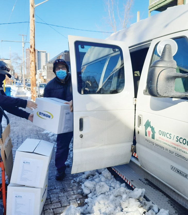 Two volunteers load a van with food boxes on a snowy day in Ottawa.