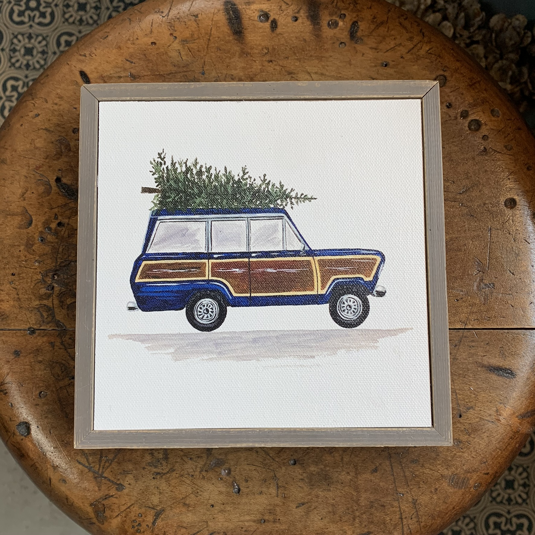 A framed picture of a station wagon carrying a Christmas tree on its roof.