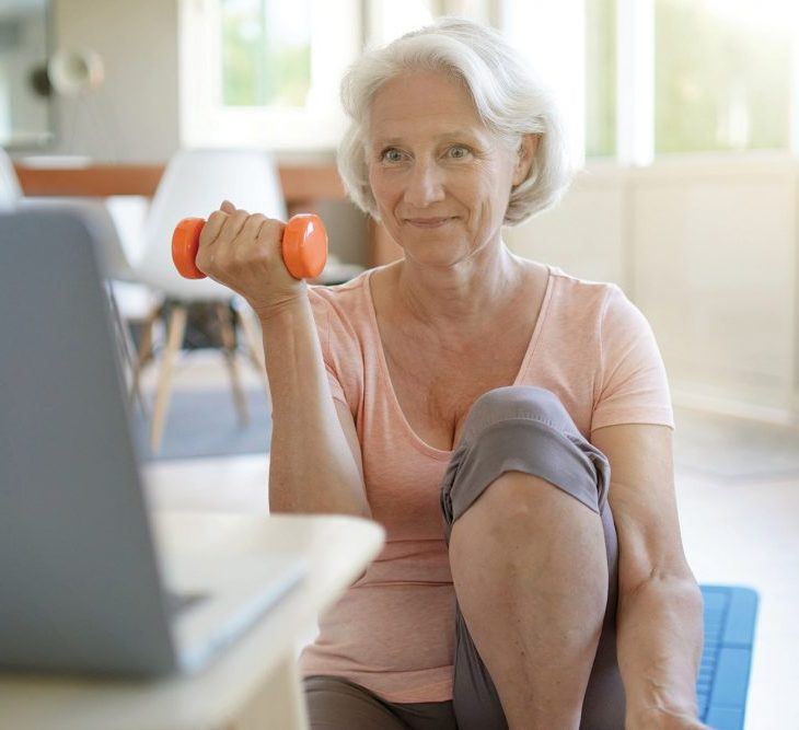 A senior woman sits on a yoga mat and uses an orange hand weight