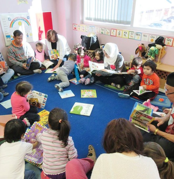 A group of adults and children participate in Ottawa Community Immigrant Services Organization's school program while sitting on the floor with textbooks and writing utensils