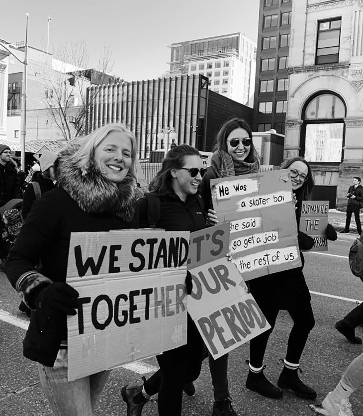 A black and white photo of MP Catherine McKenna walking in a Women's Day March in 2020 in downtown Ottawa.