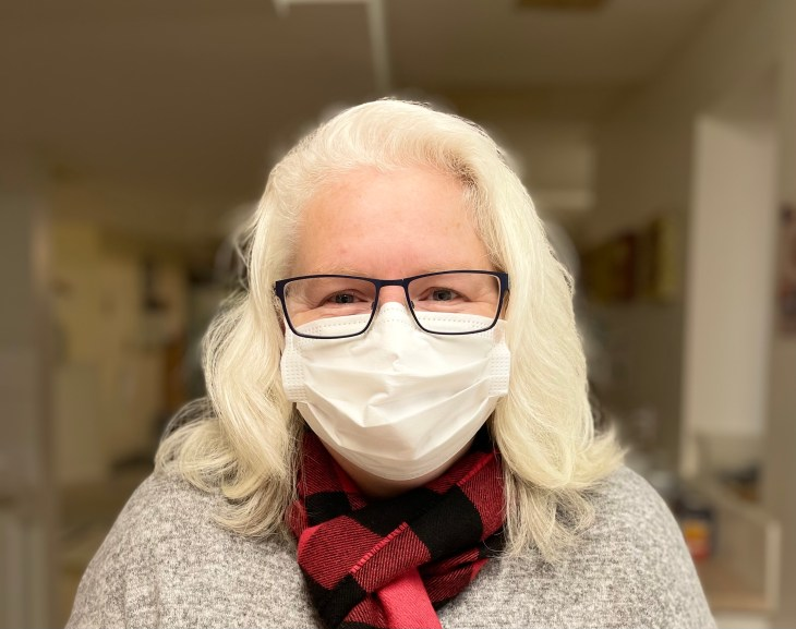 A professional headshot of a woman with white hair wearing a white face mask, glasses and red plaid scarf against a beige hallway background